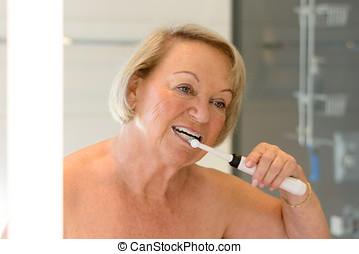 Elderly topless lady cleaning her teeth