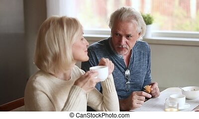 Elderly wife and husband chatting laughing feels happy...