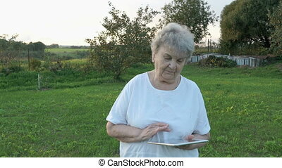 Elderly woman 80s holding computer tablet outdoors