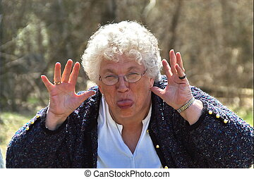 elderly woman acting silly - senior woman being silly.