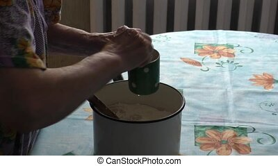 Elderly Woman adds to the dough egg