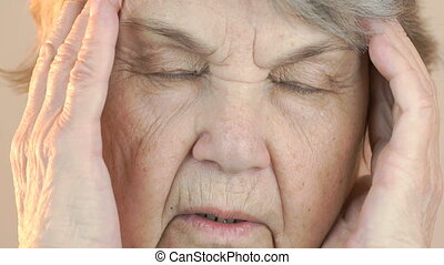 Elderly woman aged 80s suffers from headaches. Face close up