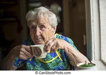 Elderly woman alone drinking tea.