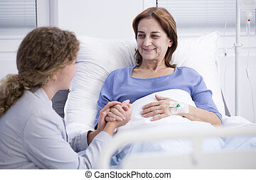 Smiling elderly woman and caring daughter in the hospital