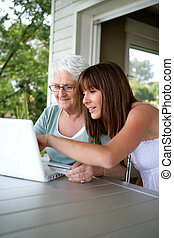 elderly woman and girl with computer