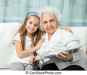 elderly woman and her granddaughter with book