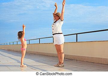 elderly woman and  little girl do morning exercise on veranda near seacoast, lifted hands upwards
