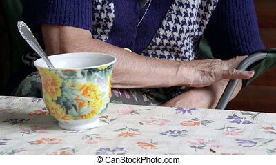 Elderly woman at the table with a cup of drink