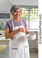 Elderly woman baking in the kitchen