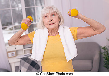 Elderly woman being tired of exercising with dumbbells