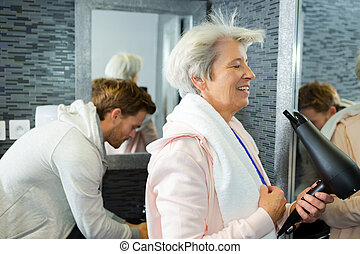 elderly woman blowdrying her hair in the gym washroom