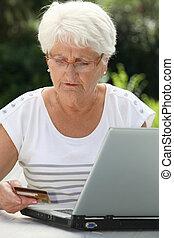 Elderly woman buying online