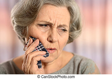 Elderly woman calling a doctor isolated on colored...