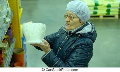 Elderly woman choosing produce in supermarket . grandmother