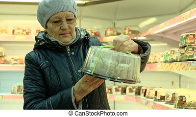 Elderly woman choosing produce in supermarket . grandmother
