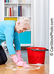 Elderly woman cleaning floor