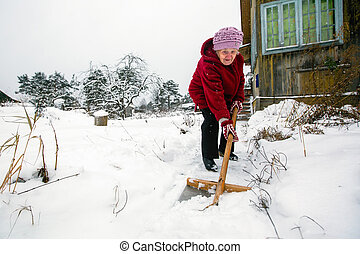 Elderly woman cleans snow near the his rural house at vinter.