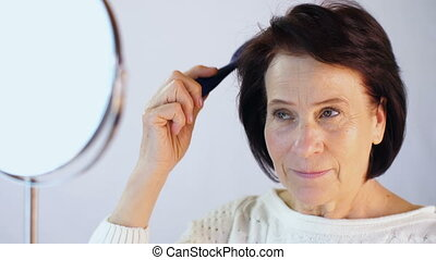 Elderly woman combing hair in front of a mirror