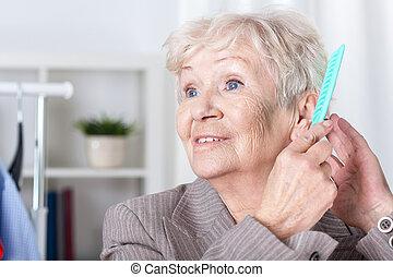 Elderly woman combing hair