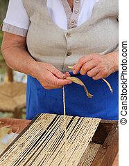 elderly woman creates straw handbags