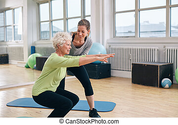 Elderly woman doing exercise with her personal trainer at...