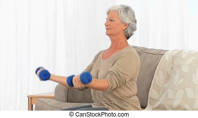 Elderly woman doing exercises on her sofa