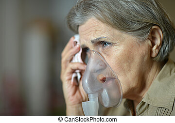 Elderly woman doing inhalation