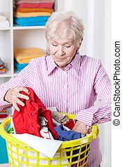 Elderly woman doing laundry