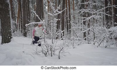 elderly woman dressed in warm sportswear is engaged in Nordic walking in the snowy woods in the fresh air. Pensioner pursuing their leisure time wading through the snow with special sticks.