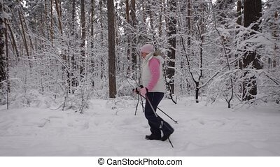 elderly woman dressed in winter sport clothes quickly goes...