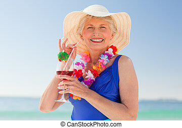 Elderly woman drinking a cocktail o