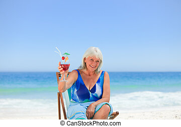 Elderly woman drinking a cocktail on the beach