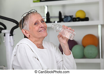 Elderly woman drinking bottled water at a gym