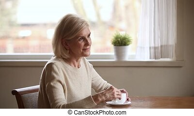 Elderly woman drinking coffee lost in pleasant thoughts and...