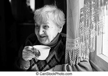 Elderly woman drinking tea.