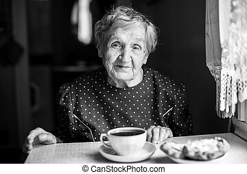 Elderly woman drinking tea in the kitchen, black and white portrait of grandmother.