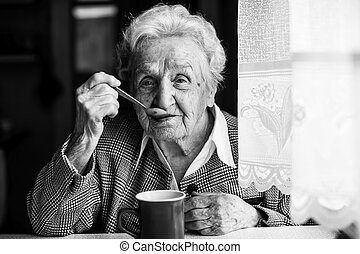 Elderly woman drinking tea sitting at the table. Black and white portrait.