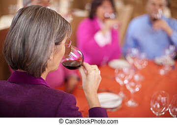 elderly woman drinking wine with friends