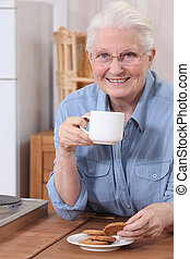 Elderly woman eating biscuits and drinking tea