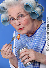 Elderly woman eating from tin can