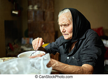 Elderly woman eating soup