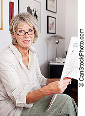 Elderly woman enjoying reading the newspaper