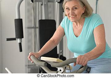 Elderly woman exercising in gym