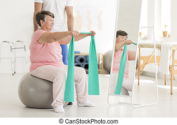 Elderly woman exercising shoulders muscles