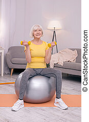Elderly woman exercising with dumbbells on a fitness ball