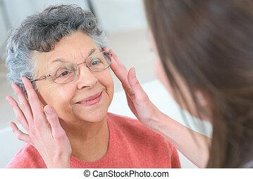 elderly woman fitting the eyeglasses
