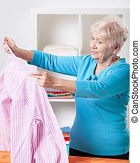Elderly woman folding shirt