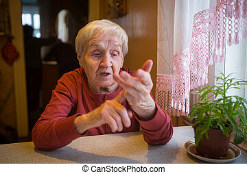 Elderly woman gesturing while sitting at the table.