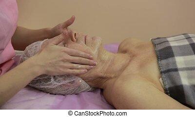 Elderly woman getting face treatment in beauty spa - Closeup...