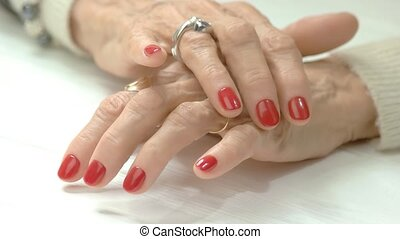 Elderly woman hands with red manicure.